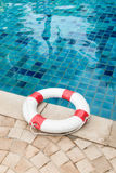 Life preserver white red lifebuoy with white ropes on tiled floo. R near swimming pool Stock Photography