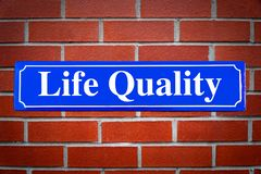 Life Quality street sign on brick wall. As symbol royalty free stock photography