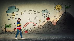 Life quest. Casual woman starting a life quest with obstacles drawn on wall. Self overcome imaginary climbing mountain with ups and downs for reaching goals stock photos