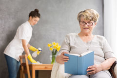 Life after retirement. Elderly women reading and caregiver cleaning her home Stock Images