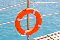 Life ring on dock. A bright orange life ring or life preserver hung on a post on a waterfront dock Stock Images