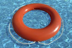 Life ring floating in water. An orange life saving ring floating in water Stock Photo
