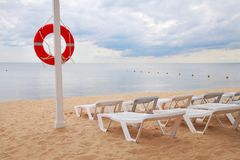 Lifebuoy and loungers. Life ring hanging on a pillar and sun beds on the beach against the sea stock images