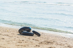 Life ring from Inner tube black color on beach in Thailand Royalty Free Stock Images