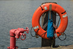 Life ring on a pier. Life ring hanging on a pier with a red valve next to it royalty free stock image