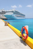 Life Ring at Port With Cruise Ships in Background. Life ring at port with docked cruise ships in background - Selective focus on foreground Royalty Free Stock Photography
