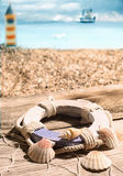 Life ring and seashells. Lying on old wooden boards draped in a fish net overlooking the beach and coast with a lighthouse in the distance Royalty Free Stock Photography