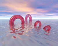 Life Rings On Ocean. Life rings sailing away into a surrise or sunset. Glasslike and translucent quality on a calm and serene imaginary sea. Reflections on water Stock Photos