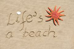 Life`s a beach written on a sandy background Stock Images