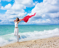 Life's Enjoyment. Pretty young woman raising her hands with fabric on beach Stock Image