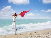 Life's Enjoyment. Pretty young woman raising her hands with fabric on beach Royalty Free Stock Images