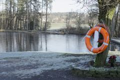 Life safety orange ring buoy at deep water private fishing lake. In the winter royalty free stock photography