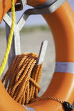 Life saver buoyancy aid with orange rope. Life saver buoyancy aid with orange nylon rope on metal stand. Focus is on rope in foreground Stock Photo