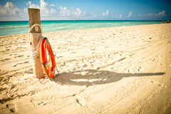 Life saver on idillic beach. Life saver beside a wood trunk on a mexican caribbean beach, located in Playa del carmen, near Riviera Maya Stock Photos