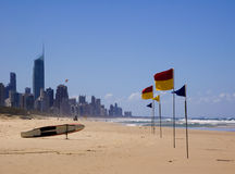Life saving at coastal city. Tall buildings on beach with surf life saving equipment and flags Stock Images