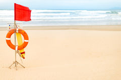 Life saving objects with red flag on beach. Stock Photo
