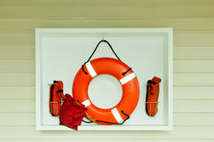 Life Saving Ring. Colorful orange life ring and other accessory lifesaving equipment hanging in a white open case on a wall.  Horizontal. Copy space Stock Photo