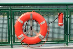 Life saving ring. Bright orange life preserver ring with attched locator beacon on side railing of passenger ferry boat Stock Photography