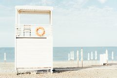 A life-saving white wooden house-tower on the seashore. Seascape, the mood of hot summer holidays and vacations, pastel oenki and bright sunny morning light royalty free stock image