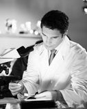 Life scientist researching in the laboratory. Life scientist researching in laboratory. Attractive young male scientist looking at the microscope slides in Stock Photography