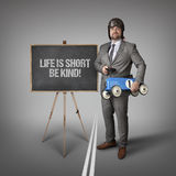 Life is short be kind text on blackboard with businessman Royalty Free Stock Photo