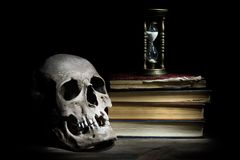 Life is short concept. Skull and vintage hourglass on old books and wooden table.  royalty free stock photos