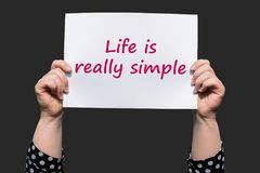Life is really simple. Motivational sign woman holding by hand royalty free stock images