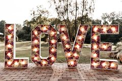 Giant flower love letters. Life-size letter filled with flowers. Illuminated love Wedding party accessory and decoration royalty free stock images