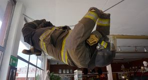 Fireman mannequin. A life size mannequin dressed as a fireman hanging in a rope as a real rescue man, demonstrative doll with fire fighter equipment as jacket Royalty Free Stock Photo