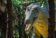 Huge dinosaur statue. Life sized huge dinosaur statue in a forest royalty free stock photo