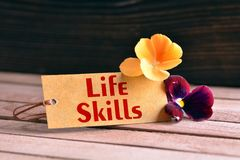 Life skills tag. Tag banner life skills and violet flower on wooden desk Royalty Free Stock Photography
