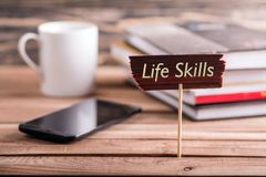 Life skills. On wooden sign with book , coffee cup and mobile phone on wooden table stock photo