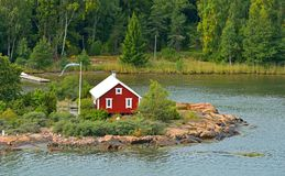 Life on small islands. Red wooden house with flag of Aland Islands, Suomi Stock Photography