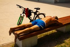 Tired cyclist resting on the bench royalty free stock image