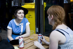 Life of street cafe. Trendy woman in blue dress and vintage hat talking with friends outside bar Stock Images