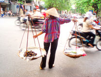Life on the street of Ho Chi Minh City in Vietman. Woman wearing traditional Asian rice hat risks the speeding mopeds of Ho Chi Minh City to sell her mangosteen Stock Photos