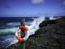 Life swimming belt on the rocky coast Stock Images