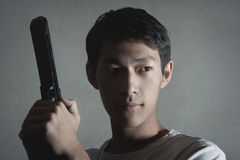 Life Threat. Portrait of the Asian guy with the gun in hands Royalty Free Stock Images