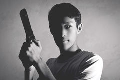 Life Threat. Portrait of Asian guy with a gun Royalty Free Stock Photos