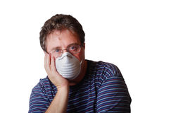 Life in today's world. A man with his head resting in his hand is wearing a face mask Stock Photography