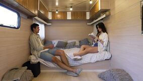 Life in the trailer. Joint evening together sitting on the bed - attractive, long haired woman reading a book while her