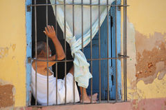 Life in trinidad, Cuba. Men behind its window Stock Photo