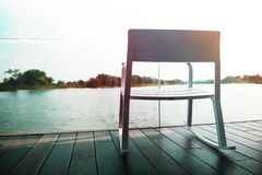 Life Unpluged Concept. Relaxing by the River. Empty Armchair on Wooden Patio Deck. Holidays Leisure and Relaxing Lifestyle. Vintage Filter royalty free stock photos