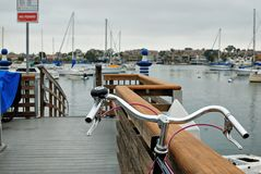 A bike on a dock looking out across the Newport Harbor towards some sailboats at mooring. royalty free stock photo