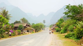 Daily life of Vang Vieng village with limestone mountains,Laos. Day time stock footage