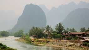 Daily life of Vang Vieng village with limestone mountains,Laos. Day time stock video footage