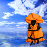 Life vest. Orange life vest rescue jacket over blue summer seascape background royalty free stock image