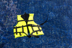 Life vest floating in swimming pool. Green life vest floating in swimming pool stock photography
