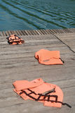 Life vest on wood floor. With a boat on river background stock photo