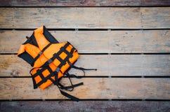 Life vest on wooden ground. Orange life vest on wooden background royalty free stock photos